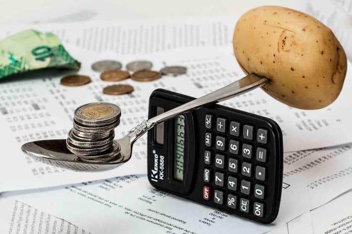 Budget personnel. Une calculatrice sur la tranche avec une cuillère en équilibre dessus supportant d'un côté une pomme de terre et de l'autre des pièces de monnaie.
