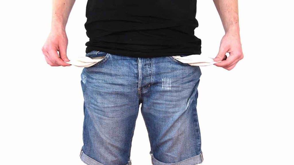 comment savoir si on est surendetté. Homme sortant l'interieur des poches de son jean.