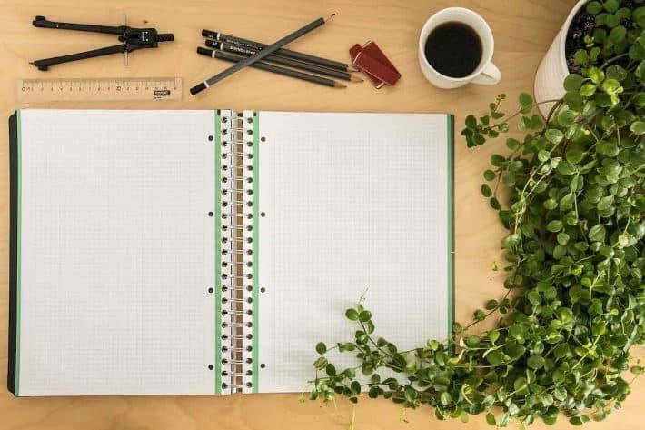 Faire un cahier de compte maison. Cahier vue de dessus, compas, crayon et tasse de café.