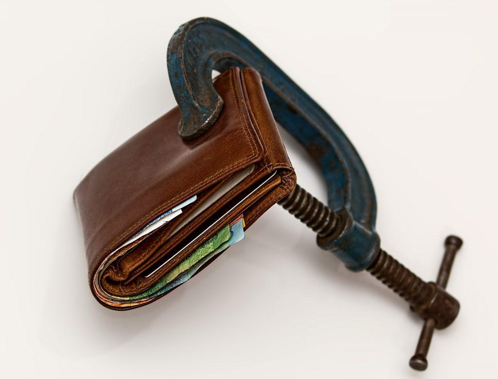 Un portefeuille fermé maintenant dans la prise d'un mini-étau.