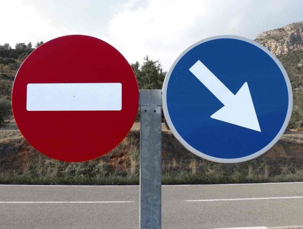 Deux panneaux de signalisations. Un sens interdit et obligation de direction. La motivation par obligation pour Vaincre la procrastination.