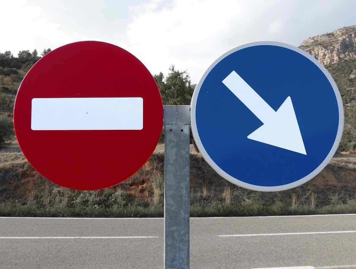 Ne plus procrastiner. Un panneau de sens interdit et un panneau de direction obligatoire.