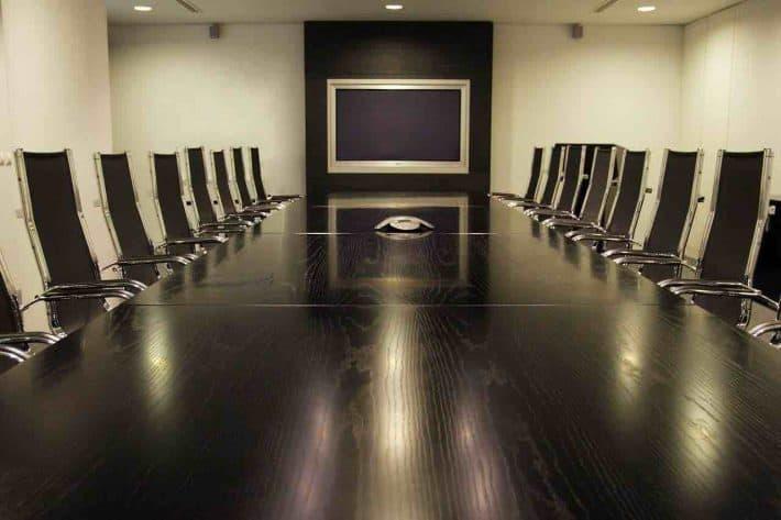 Commission de Surendettement/ Une longue table de réunion et des chaises.