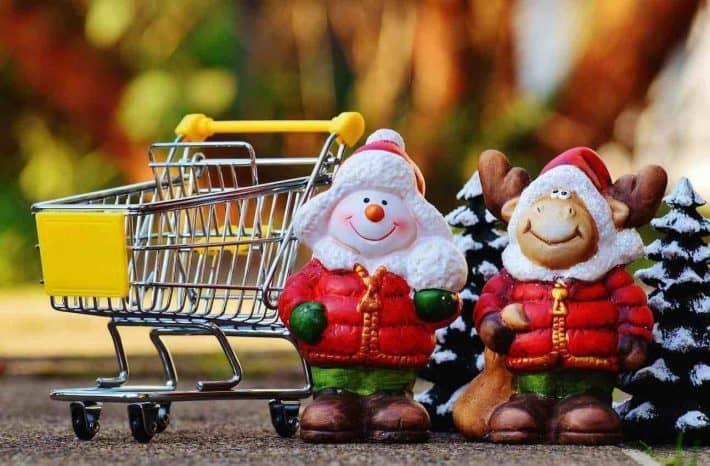 Gagner de l'argent en offrant des cadeaux de Noël. Des figurines de père Noël à cotè d'un caddie.