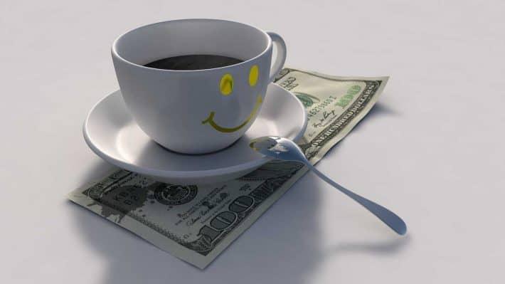 Comment faire des économies de façon intelligente. Une tasse de café souriante sur un billet de 100 dollars.