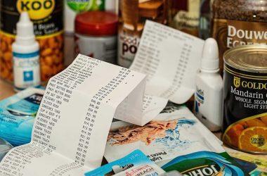 Être pauvre ça coûte cher. Un ticket de caisse et des boîte de conserve autour.