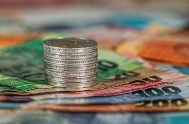 Faire des économies sans changer son mode de vie. Une pile de pièces de monnaie sur un tas de billets de banque.