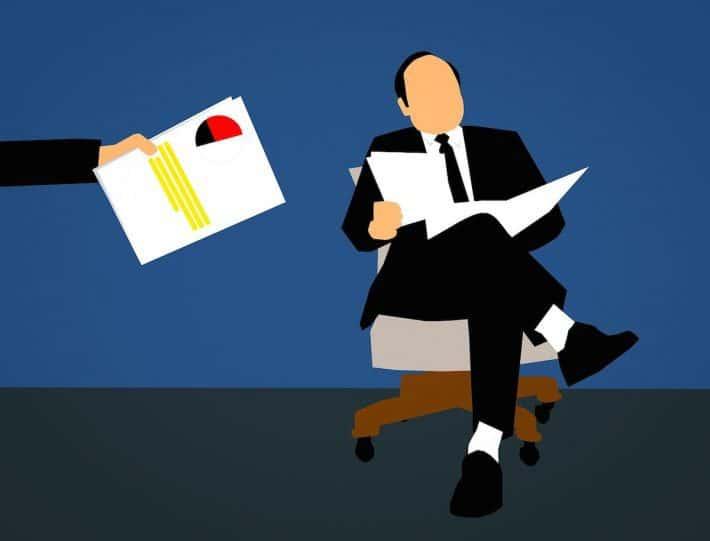 Rendez-vous avec un conseiller bancaire. Un homme assit lisant le journal.