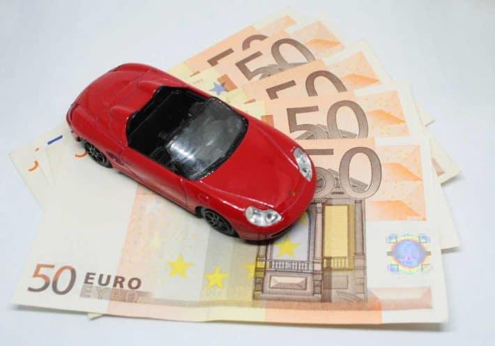 Économiser sur sa voiture. Le budget auto. Une miniature de voiture sur des billets de banque.