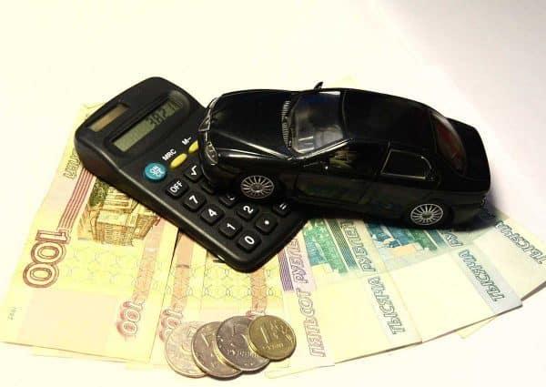 Économiser sur son budget voiture. Une calculette, une mini voiture et des billets de banque.