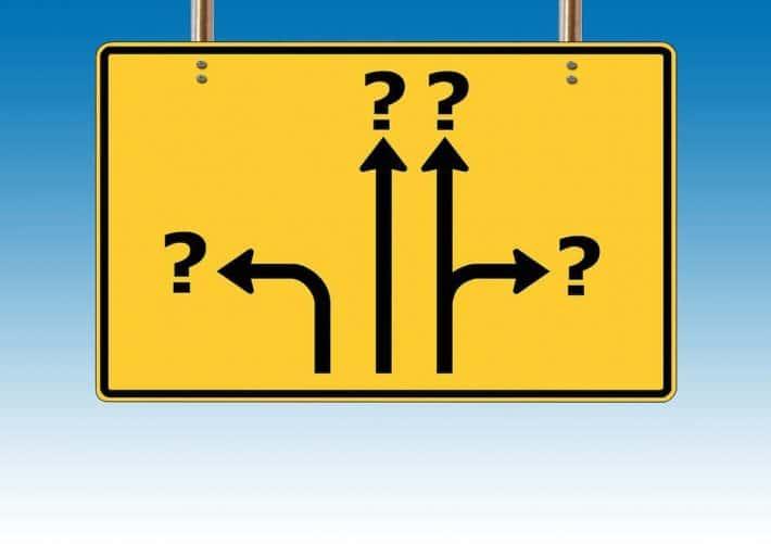 Choisir de devenir riche, c'est possible ? Un panneau de signalisation avec des directions se finissant par un point d'interrogation.