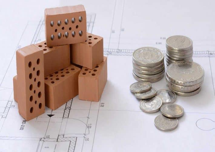 Programme d'épargne. Des briques de constructions sur un plan avec de la monnaie.