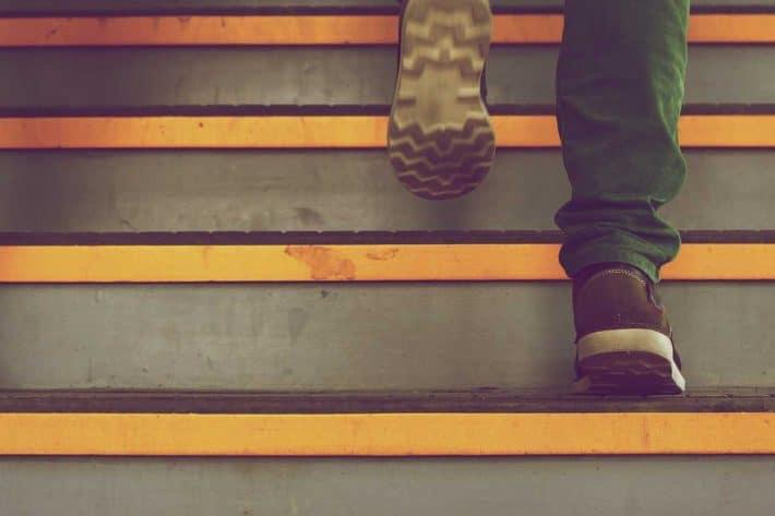 10 règles pour bien épargner son argent. Des pieds montant des marches d'escalier.