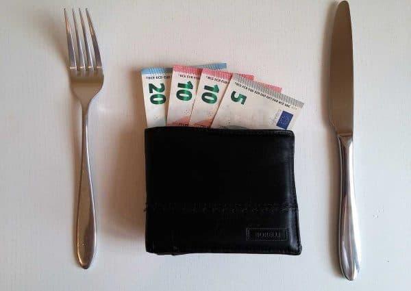 Comment être riche. Portefeuille avec des billets de banque entourè d'un couteau et d'une fourchette.