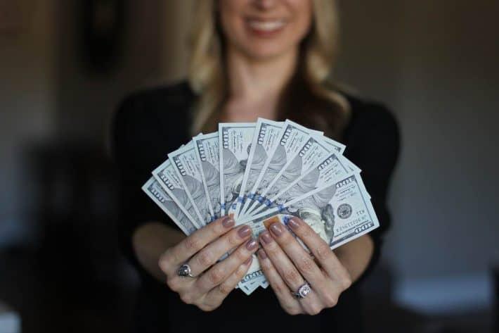 Augmenation de salaire. Une femme presentant des billets de banque.