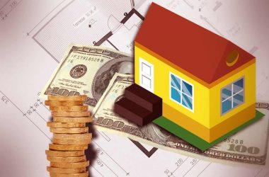 Gérer son patrimoine financier. Maquette d'une maison, des billets de banque et des pièces de monnaie.