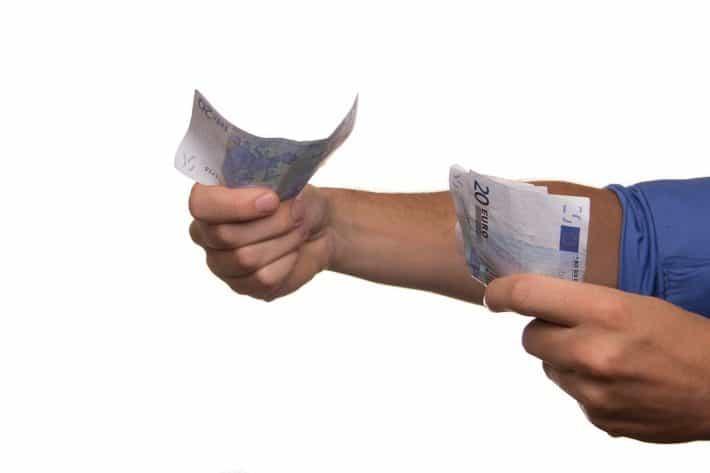 Negocier son salaire. Des billets de banque tendue à quelqu'un.