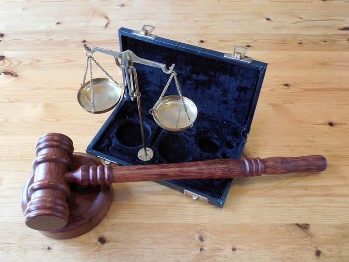 Effacement de dette. Un marteau de juge et une balance de justice.