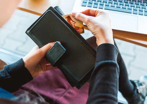 Se payer en premier. Une carte bancaire que l'on sort d'un portefeuille..