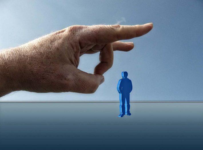 Réforme chômage 2019. Une main géante mettant une pichenette à un humain.