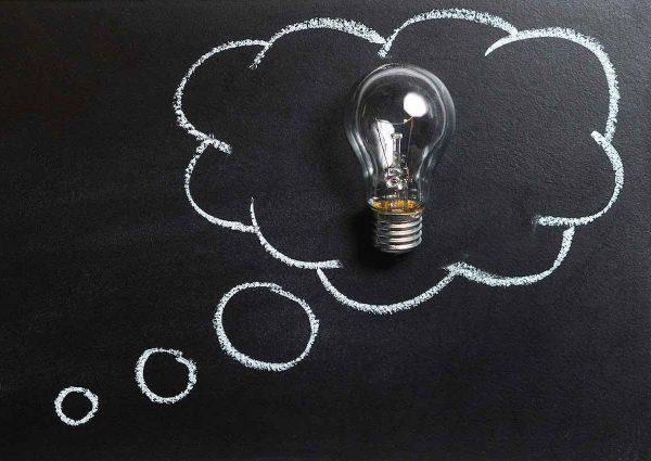 Comment trouver une bonne idée d'affaire. Une bulle de pensée sur un tableau noir avec une ampoule à l'intérieur.