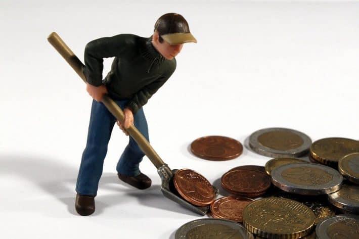 Découvert bancaire que faire ? Homme munie d'une pelle ramassant des pièces.