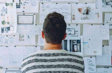 Pourquoi créer sa propre entreprise. Un homme devant un tableau remplit de fiches et de notes.