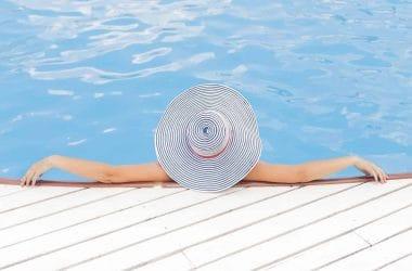 combien d'argent faut-il pour vivre sans travailler. Une femme sur le bord d'une piscine avec un chapeau de pailles.