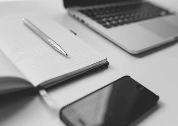 comment gagner de l'argent en travaillant en ligne. Ordinateur portable, smartphone, stylo et carnet blanc.